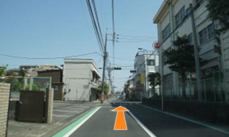 小学校を通り過ぎたところに手押し信号があります。信号の近くまで行くと左側に看板が見えます。